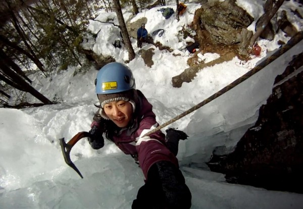 An ice climber ascends an icy outcropping
