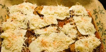Layer on mozzarella, grated parmesan, sprinkle with cayenne...