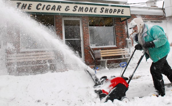 Frank Coglitore clears snow on Dec. 15 in front of Cigar Shop on Main Street in Bangor. BDN photo by Terry Farren.