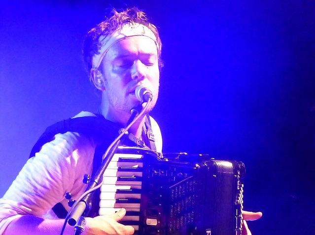 In this Lesley Keller pic, Mumford & Sons accordion player Ben Lovett plays and sings. Great stage color here.