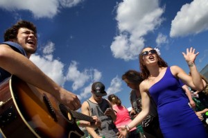 "Zach Silk (left) and Kayla Bannister belt a song while waiting in line to audition for a spot on the television singing competition ""American Idol"" in July on the Maine State Pier in Portland. (BDN photo by Troy R. Bennett)"