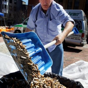 "Mike Roylos of Portland's Spartan Grill shovels up about 68,000 cigarette butts collected in recent weeks around the city in his ""buttlers,"" cylindrical ash trays attached to utility poles and street signs. Troy R. Bennett 