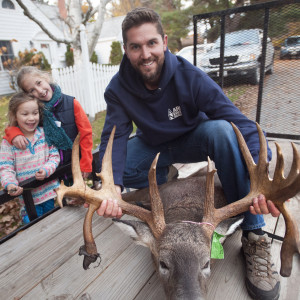 Ben Thibodeau poses with the deer he shot in Bucksport on the opening day of the hunting season in 2015. He said he did not hunti growing up and this is the first deer he shot since taking up the activity three years ago.  At left are Thibodeau older daughters Mirabel, 5, (left) and Zoe, 8. (BDN photo by Gabor Degre)