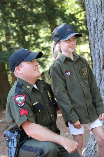 "Maine game warden Scott Thrasher, who stars on the Animal Planet TV show ""North Woods Law,"" poses with Lauren Weber, 8, of Cumberland, on Sept. 28, at the Maine Wildlife Park in Gray."