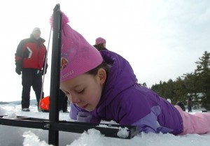 BDN photo by Kate Collins Mikayla McMullen, 8, of Orrington examines an ice-fishing trap during the first of several winter camping days at Camp Capella on Phillips Lake in Lucerne on Jan. 29, 2011.