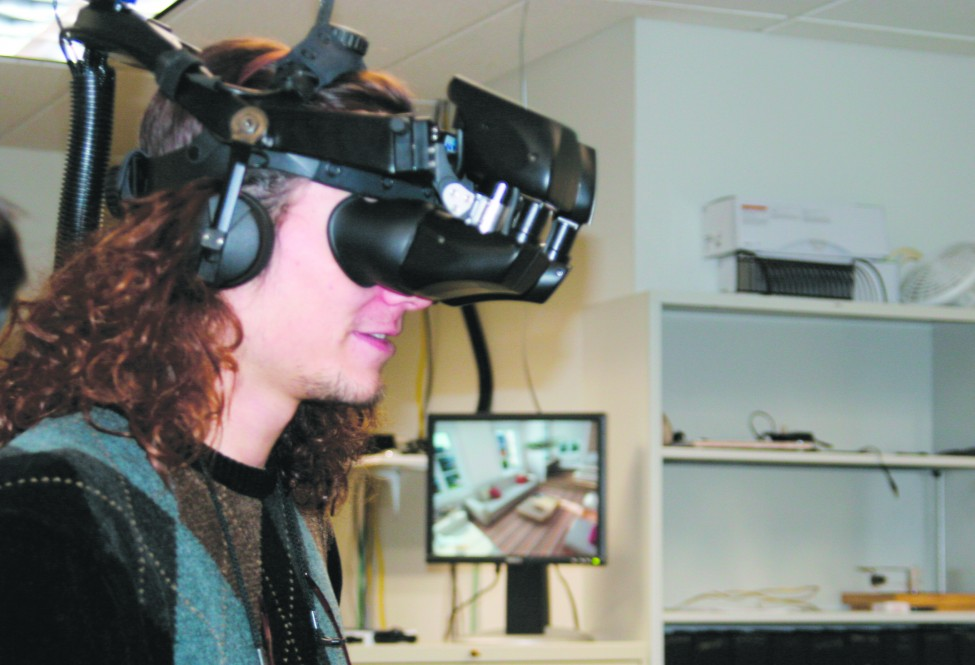 Rob Stigile, Maine Campus features editor, tries on the Head Mounted Display at the VEMI lab.