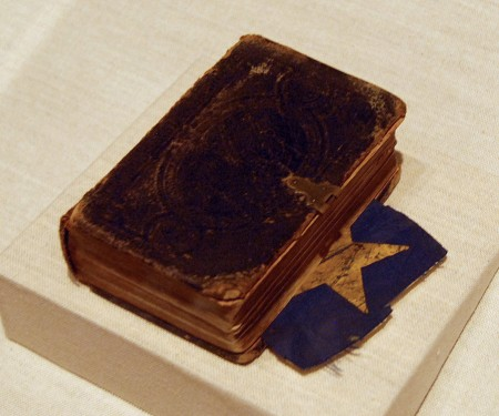 "When Sgt. Jonathan Edward McPhee of Co. F, 16th Maine Infantry Regiment, was captured at Gettysburg on July 1, 1863, he hid in his pocket Bible a fragment of the national flag carried into action with the regiment. Soldiers tore up the flags and hid the fragments in their uniforms and elsewhere so their Confederate captors could not seize the intact flags. Later released, McPhee rejoined the regiment. He was killed when a bullet struck his heart during the April 1865 Battle of Five Forks, Va. McPhee's Bible and flag fragment are on display in the Maine State Museum's ""Maine Voices in the Civil War"" exhibit. (Brian Swartz Photo)"