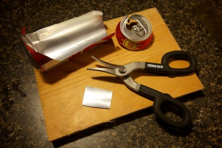 To make a pinhole for your pinhole camera, start with a square cut from a soda can.