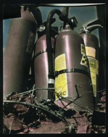A hand colored 4x5 contact print some old fire extinguishers I made with a pinhole camera I made with a Christmas cookie tin and a soda can.