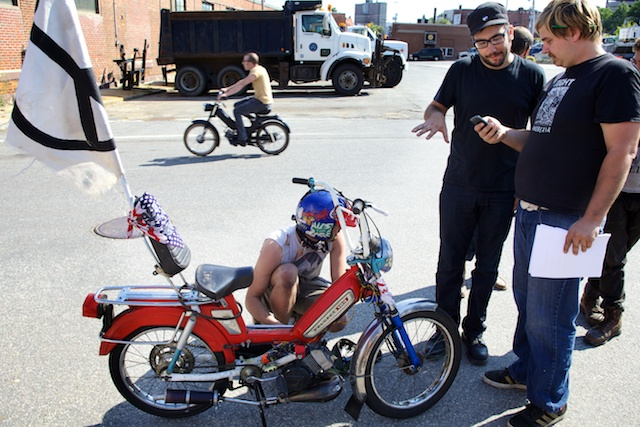 Steve Sabat works on his Peugeot moped while Pinball Run organizer Rob Burrito (right) shows a Mars (a moped rider with one name) a tracking app on his phone in Portland Friday. Troy R. Bennett | BDN