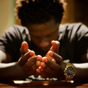 06/21/15 -- Christian Irutingabo, 18, prays in church on a Sunday in Portland. Fleeing violence in Burundi, Irutingabo and his sister arrived in the city last fall knowing no one. The General Assistance program has allowed them to survive and go to Deering High School. Troy R. Bennett | BDN