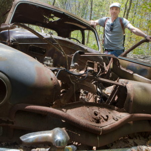 "Photographer David Hill revisits one of the abandoned cars he photographed for his award-nomintaed book ""Full Service"" in a secluded patch of woods in Westbrook on Tuesday. He first found the car, a 1950 Plymouth, while working a story for his day job as a television news photojournalist. Troy R. Bennett 