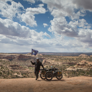 I held the Maine flag aloft while standing on the rocks on the west side of the Monitor and Merrimac Buttes north of Moab, Utah. Dom Chang took the photo for me.