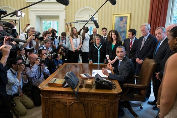 President Barack Obama looks back towards a group of students before signing H.R. 1911, the &quotBipartisan Student Loan Certainty Act of 2013,&quot in the Oval Office, Aug. 9, 2013.