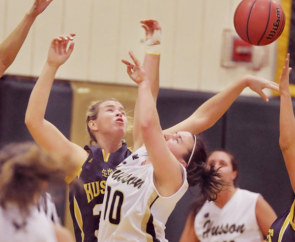 USM women's basketball player Courtney Cochran, back , blocks a shot by Husson player Caitlyn Butterfield (10) in the first half of their game in Bangor, Maine, Tuesday, Jan. 3, 2012.