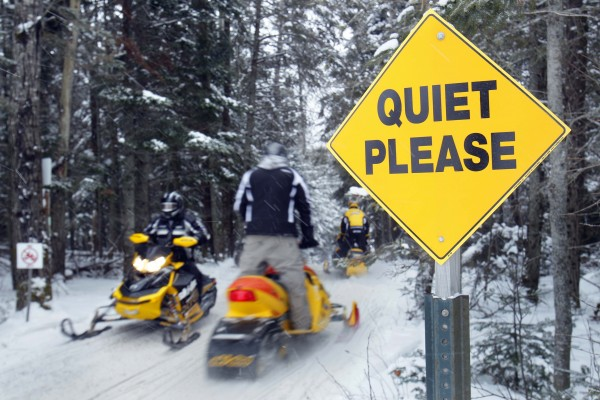 Snowmobilers travel a trail leading to Rangeley Lake during the Snodeo, Saturday, Jan. 21, 2012, in Rangeley, Maine. Several hundred riders descended on Rangeley for the annual celebration of snowmobiling.