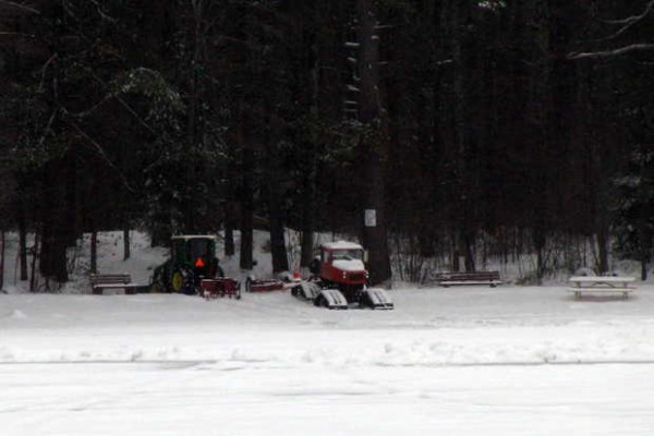 Equipment to create a 660-foot-long track for the Norway Trackers snowmobile club's snowmobile races this weekend on Lake Pennesseewassee was parked Friday after weather conditions forced cancellation of the event.