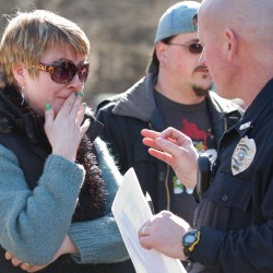 An unidentified parent of a Walpole Elementary School student speaks to a police officer outside the school where a 14-year-old male student shot himself in front of many classmates in the school's cafeteria in Walpole, N.H. on Friday, Feb. 10, 2012.