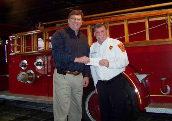 Chief Gary Parent of the Brewer Fire Department presents a check for pledges to encourage his jumping into the Polar Plunge to Dana Mosher, executive director of Camp CaPella.