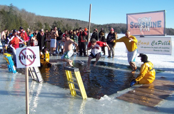 Chief Gary Parent of the Brewer Fire Department, in the middle wearing a Red Sox T-shirt, jumps into frozen cold Phillips Lake at the Camp CaPella Polar Plunge on Sunday, Feb. 5.