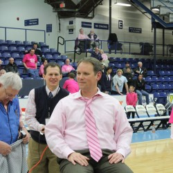 UMaine women's basketball coach sits at center court Wednesday night at Alfond Arena in Orono as Erv Morrison (left) of Erv's Barber Shop in Orono and UMaine athletics associate athletic director Joe Roberts make preparations to shave Barron's head. UMaine helped raise more than $10,000 for breast cancer research and awareness.