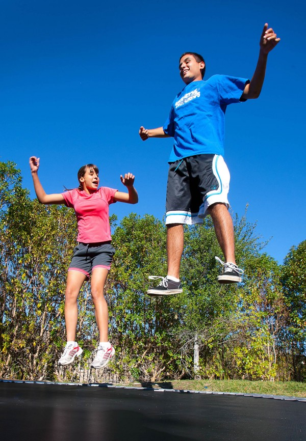 Fraternal twins Noah and Alexis Beery get some air on the family trampoline at home in Olivenhain, Calif. Genome sequencing revealed that the twins had been misdiagnosed and incompletely treated for an illness that had caused vomiting, muscle weakness and seizures for more than a decade.