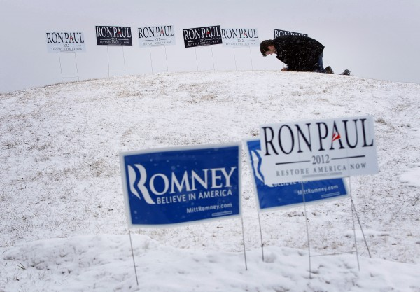 Mike Donahue plants signs in frozen ground in support of Republican presidential candidate Ron Paul outside a caucus, Saturday, Feb. 11, 2012, in Portland, Maine.