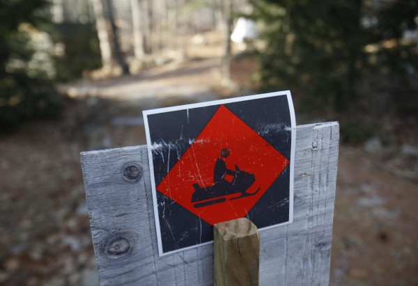 A snowmobile trail sign marks a trail, Thursday, Jan. 5, 2012, in Bridgton, Maine. Snow lovers are still waiting for the white stuff throughout much of the Northeast.