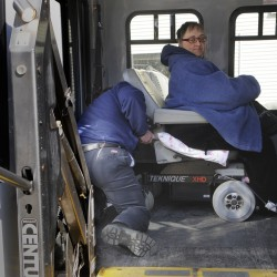 Penquis Lynx bus driver Ronald Cote buckles Sandra Rocco of Bangor and her wheelchair in place after she used a chair lift to board the bus for her departure from Penquis in Bangor Tuesday, Feb. 21, 2012.