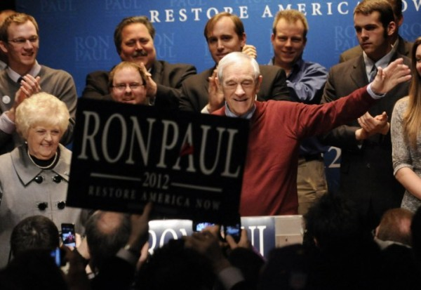 Republican presidential candidate Rep. Ron Paul, R-Texas, waves to supporters as he arrives to address them during his caucus night party Tuesday, Feb. 7, in Golden Valley, Minn. At left is Paul's wife Carol.