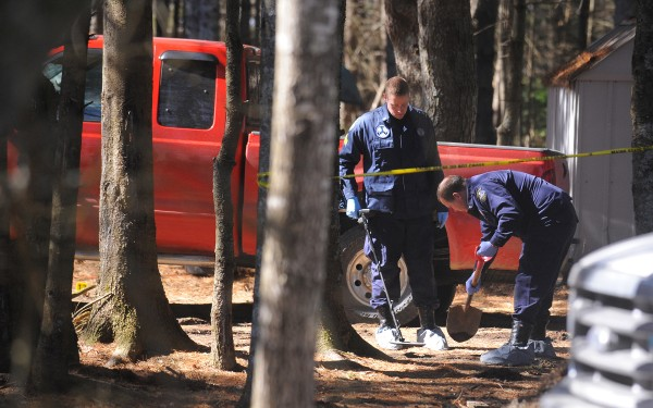 Maine State Police search the grounds for evidence with a metal detector on Monday, March 12, 2012 around the Lamoine home where four people were shot early Sunday morning.