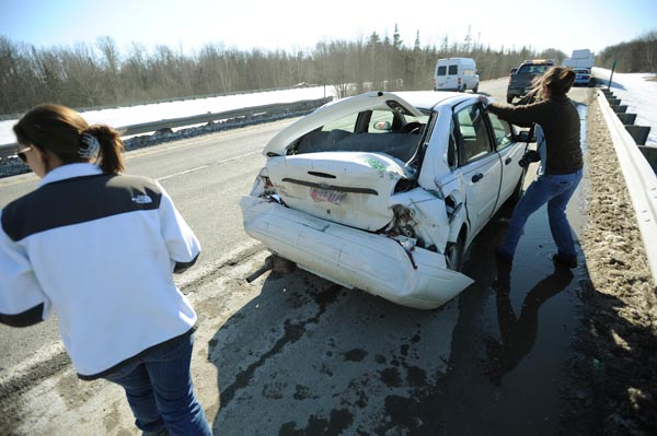 Gloria Ripley (right) of Sidney, tugs on the door of her car along I-95 in Hampden on Tuesday, March 6, 2012 after being rear-ended by a tractor-trailer truck. With Ripley is her daughter Erin (left) who was being picked up in Bangor by her mother. The two waited until Ripley's other daughter drove up from Sidney to pick them up. No charges were filed. The driver of the tractor-trailer, David Marberry of Houma,  Louisiana, continued to Virginia with his load of lumber.