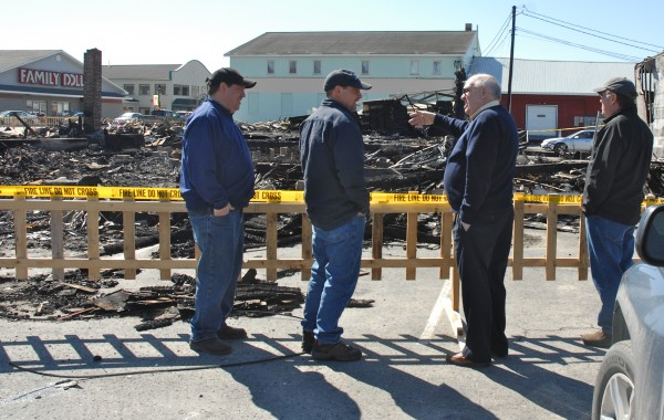 Two generations of the Labbe family look over the pile of rubble that had been Nadeau's House of Furniture on Tuesday, March 27, 2012. The building, along with two others, was destroyed in an early morning fire on Sunday. Ellery &quotArms&quot Labbe (second from right) purchased the furniture business in 1975 and operated with his sons Dave (left), Phil (second from left) and Pat (right). A separate nearby flooring business owned by Dave Labbe was saved.