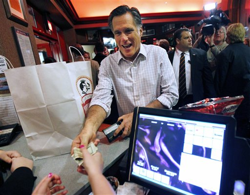 Republican presidential candidate Mitt Romney pays for his takeout order at the Montgomery Inn in Cincinnati on Saturday, March 3, 2012.