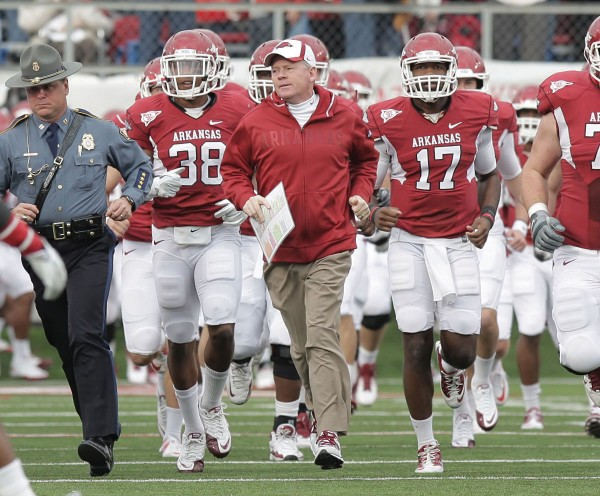 In this Nov. 19, 2011, photo, Arkansas football coach Bobby Petrino, center, leads the Razorbacks onto the field with Arkansas State Police Capt. Lance King, left, before a game against Mississippi State in Little Rock, Ark. Arkansas fired coach Petrino on Tuesday, April 10, 2012, publicly dressing him down for unfairly hiring his mistress and intentionally misleading his boss about everything from their relationship to her presence at the motorcycle accident that ultimately cost him his job.