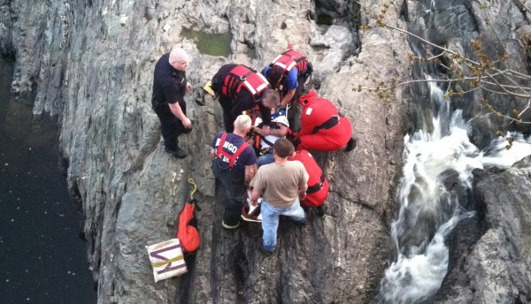 Members of the Bangor Fire Department tactical rescue team bring Ryan King of Bangor up the banks of the Kenduskeag Stream below the Kenduskeag Stream Park in Bangor on Tuesday, April 17, 2012. King broke both legs and suffered other injuries after attempting to leap down onto a ledge from the park observation deck. Former EMT Josey Mackin of Brewer jumped into the water, lifted King's head up out of the water, and brought him to the shore. He then checked King's injuries and kept him awake while waiting for emergency personnel.