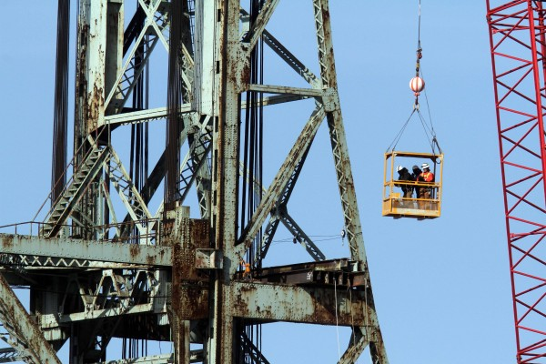 A work crew is lifted to one of two towers of the historic Memorial Bridge connecting New Hampshire to Maine, Wednesday, Feb. 8, 2012 in Portsmouth, N.H.