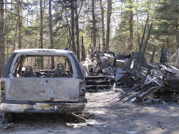 A burnt-out SUV sits next to the Waltham trailer that was destroyed by a fire on Thursday, April 5, 2012. Senior Investigator Ed Archer with the Maine state fire marshal's office can be seen sifting through the debris to attempt to determine what sparked the fire that displaced a young family. However, officials said later Friday that the damage was too severe to determine a cause.