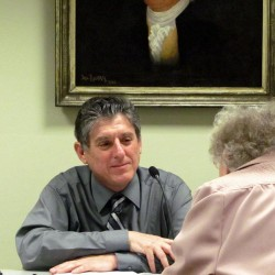 Roger Raymond talks to a long-time former in Bucksport's town office on Thursday, April 19, 2012, during Raymond's final meeting as town manager. Raymond retired last week after 27 years with Bucksport.