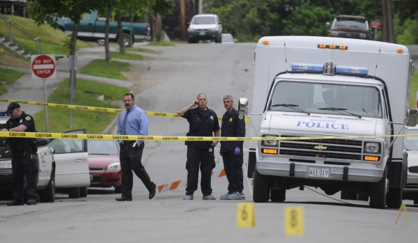 Bangor Police Detective Larry Ellis (center left) and Sgt. Paul Edwards (center right) confer while they help fellow officers investigate the area of a fatal stabbing on First Street in Bangor that took place there early Tuesday, May 22, 2012.