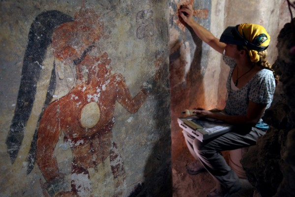 Conservator Angelyn Bass cleans and stabilizes the surface of a wall of a Maya house that dates to the ninth century in the Mayan city of Zultun in northeastern Guatemala.