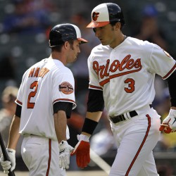 Ryan Flaherty (right) of the Baltimore Orioles low-fives J.J. Hardy after hitting a solo home run in the first inning of the first baseball game of a doubleheader against the Texas Rangers in Baltimore on Thursday, May 10, 2012.
