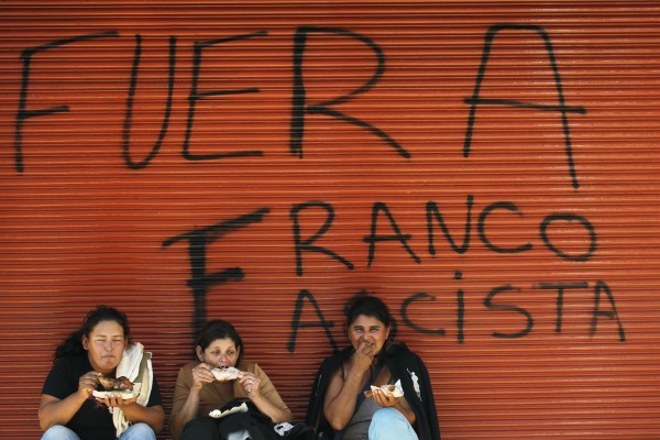 Supporters of Paraguay's ousted President Fernando Lugo eat chicken against a wall spray painted with a message that reads in Spanish: &quotOut Franco, fascist, &quot referring to Paraguay's newly named President Federico Franco, in Asuncion downtown, Paraguay, Tuesday, June 26, 2012. Lugo has surprised Paraguayans with conflicting announcements since the Senate voted to remove him from office last week. At first, he said he would comply and leave office. Then, he said he would fight the decision and make his case to the region's leaders.
