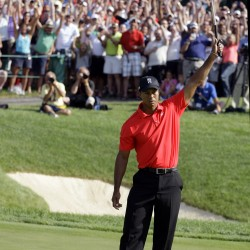 Tiger Woods raises his putter after making a birdie putt on the 18th hole during the final round of the Memorial golf tournament, Sunday, June 3, 2012, in Dublin, Ohio.
