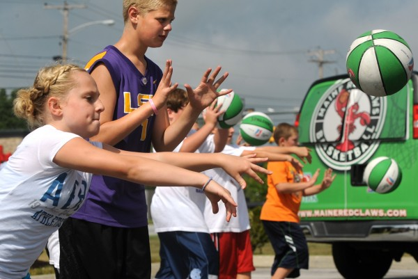 Elizabeth White, 11, of Veazie (left) and 14-year-old Sam Brown of Lee hone their passing skills in August 2010 during a Maine Red Claws basketball clinic in Brewer. They were among 25 youngsters who participated in the clinic conducted by Red Claws coach Austin Alinge.
