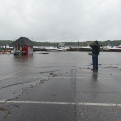The space between this spectator and boats docked off Commercial Street in downtown Bath usually includes a parking lot and a row of boulders but the shoreline moved considerably on Monday.