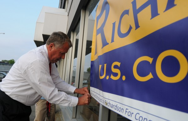 2nd District congressional candidate Blaine Richardson tapes a banner on a store front next to Hero's sports bar in Bangor before attending his primary night party there Tuesday evening, June 12, 2012.