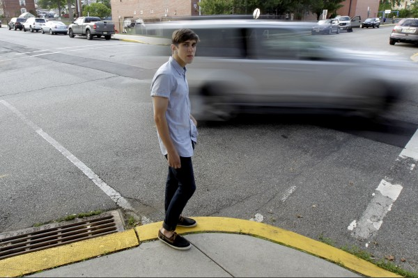 Dylan Young, 18, poses for The Associated Press as a vehicle cruises by, Wednesday, June 6, 2012, in North Arlington, N.J. Young, a senior at North Arlington High, was in a fender-bender accident caused by being distracted while texting and driving. More than half of high school seniors say they text or email while driving, according to a jarring new study that offers the first federal statistics on how common the dangerous habit is in teens.