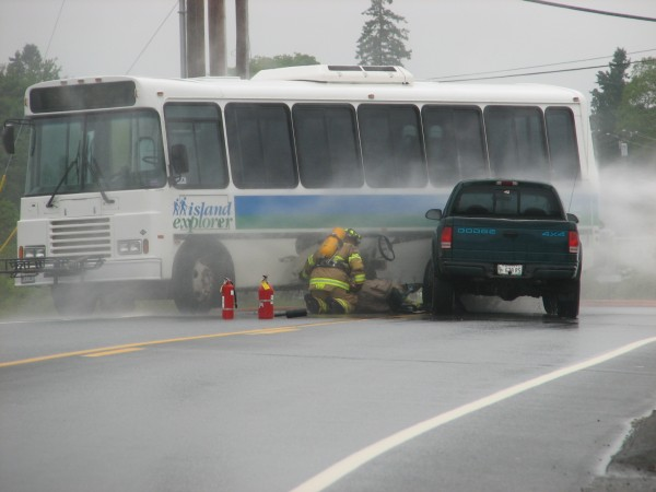 Firefighters examine a propane fuel tank on a Downeast Transportation bus that was struck by a pickup truck Wednesday, June 13, 2012, on Route 3 in Trenton. Concerns about gas leaking from the tank resulted in the road being closed and hundreds of motorists stranded for several hours. The vehicles eventually were moved and the road reopened after firefighters let all the gas leak out of the tank.