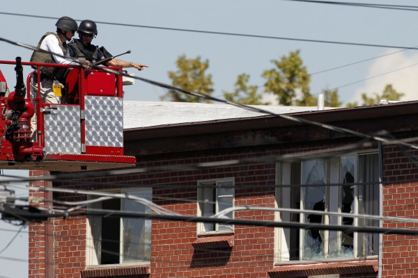 Members of law enforcement wearing body armor and helmets use fire department apparatus to look in the apartment of alleged gunman James Holmes on Saturday, July 21, 2012 in Aurora , Colo.